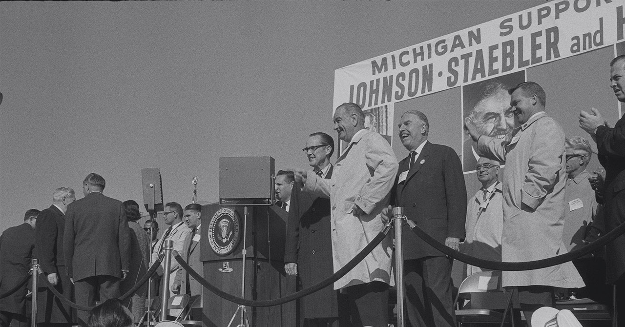 President Johnson on stage with a group at a campaign rally