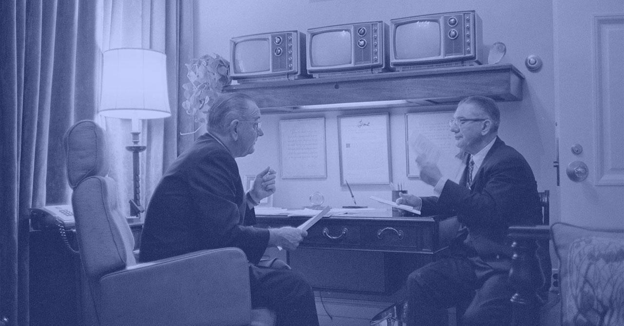 President Johnson and Wilbur Mills talking at a desk