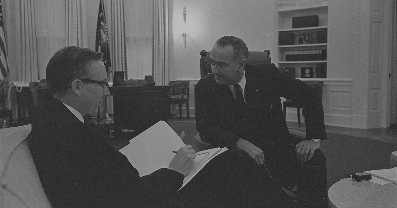 LBJ sitting and talking to Walter Heller