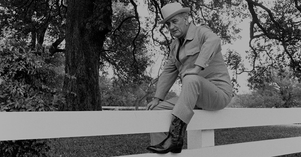 LBJ wearing cowboy boots, sitting on a fence