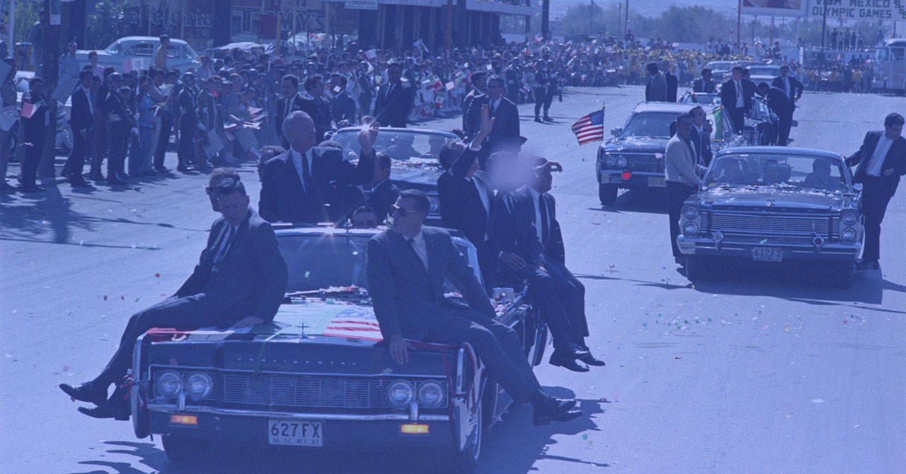 LBJ in a car, waving to a crowd, surrounded by Secret Service officers