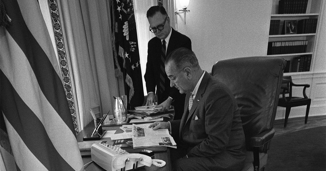 LBJ sitting at a desk with White House aide Walter W. Jenkins standing behind him
