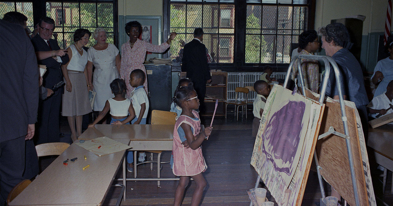 Lady Bird Johnson gets a tour of a classroom with students in it