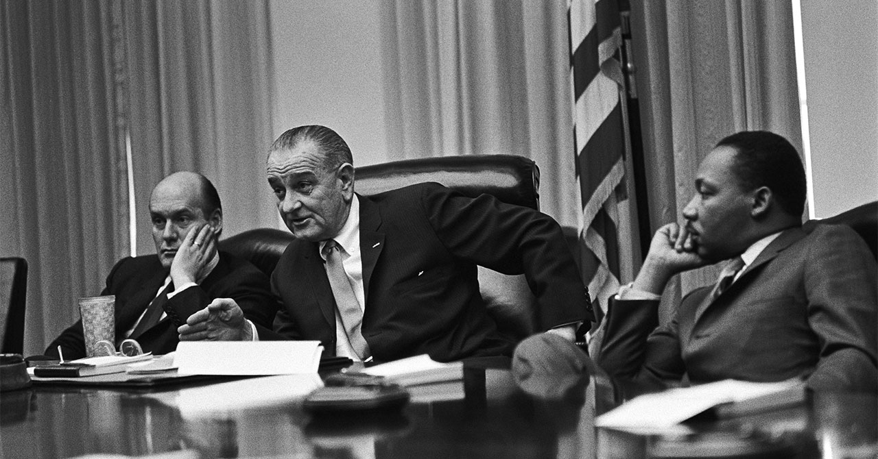 LBJ and Martin Luther King Jr. sitting at a table during a meeting