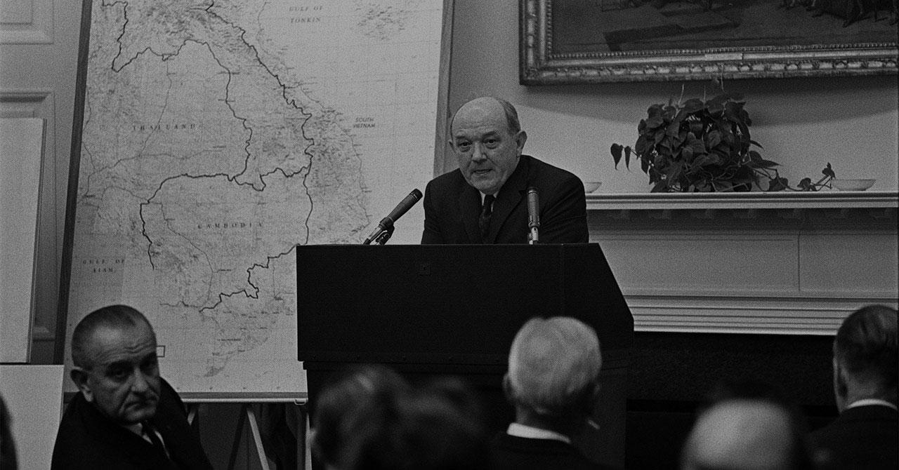 Dean Rusk standing behind a podium next to a map of Vietnam