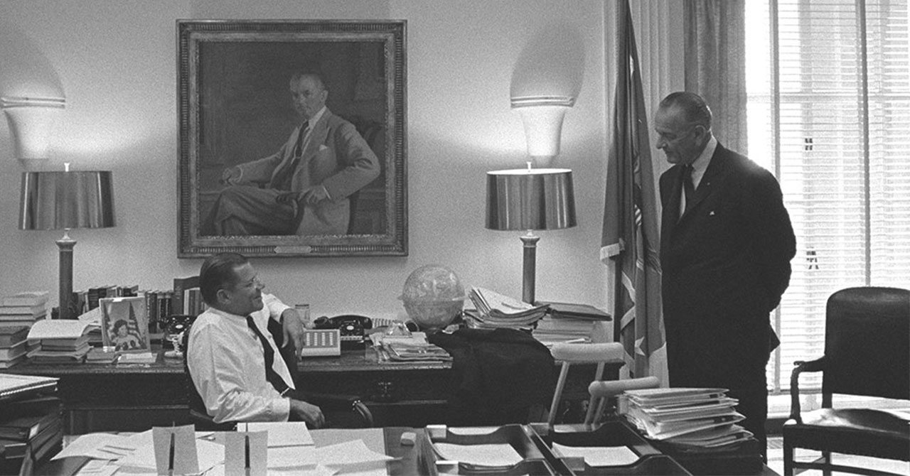 Robert McNamara sitting and talking to LBJ standing