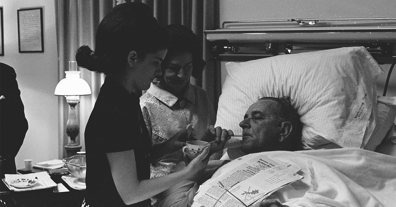 LBJ sipping through a straw while Lady Bird and Luci stand by his bed