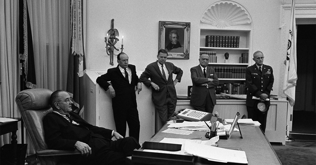LBJ sitting down surrounded by aides