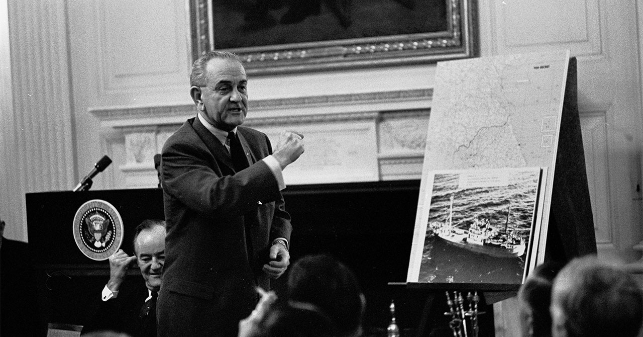 LBJ standing and talking in front of a photo of the USS Pueblo