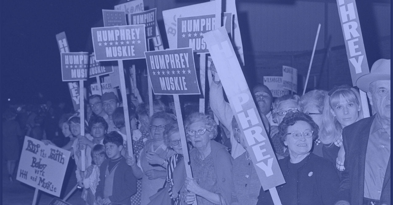 people in a crowd holding Humphrey/Muskie signs during the 1968 presidential campaign
