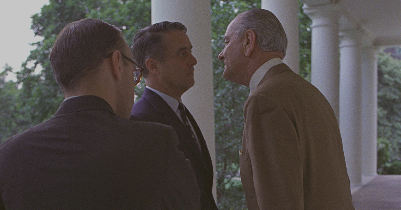 """President Johnson giving the """"Johnson treatment"""" (leaning in close) to Sargent Shriver"""