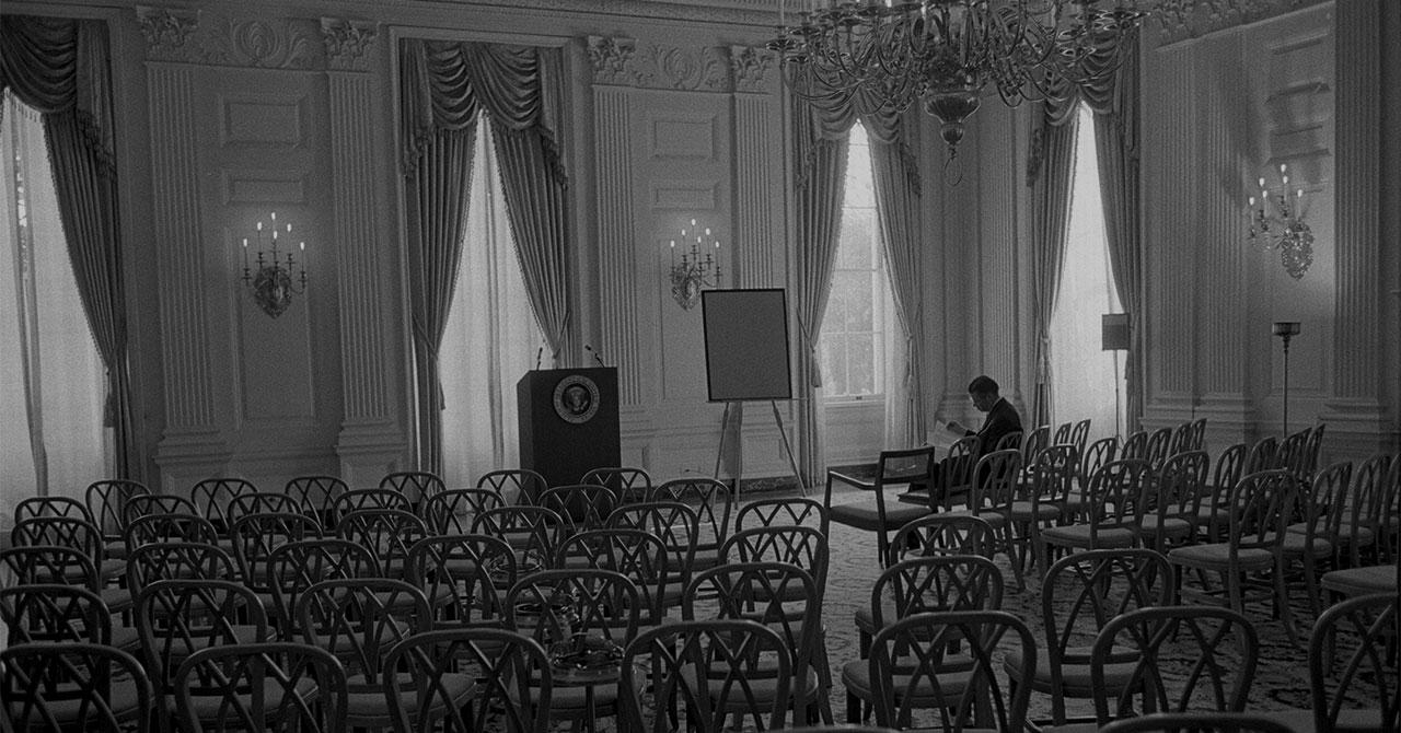Robert McNamara sitting by himself in an empty room