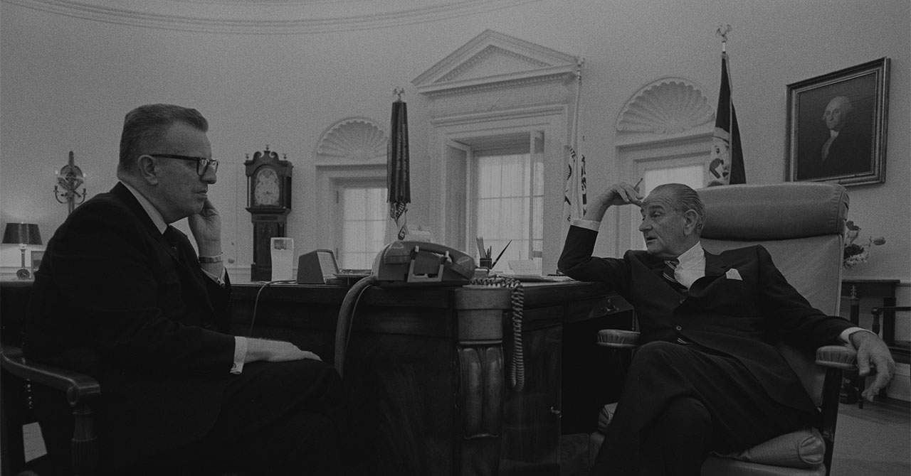 Larry O'Brien and LBJ sit around a desk in the Oval Office