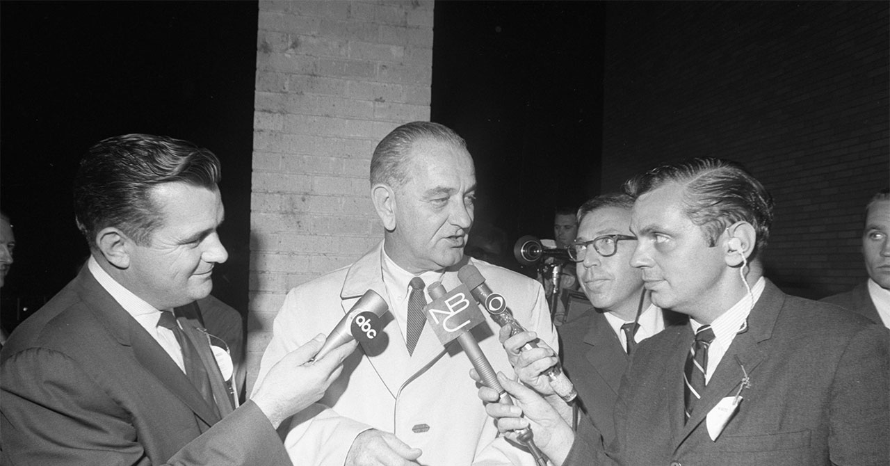 LBJ talking to reporters holding microphones