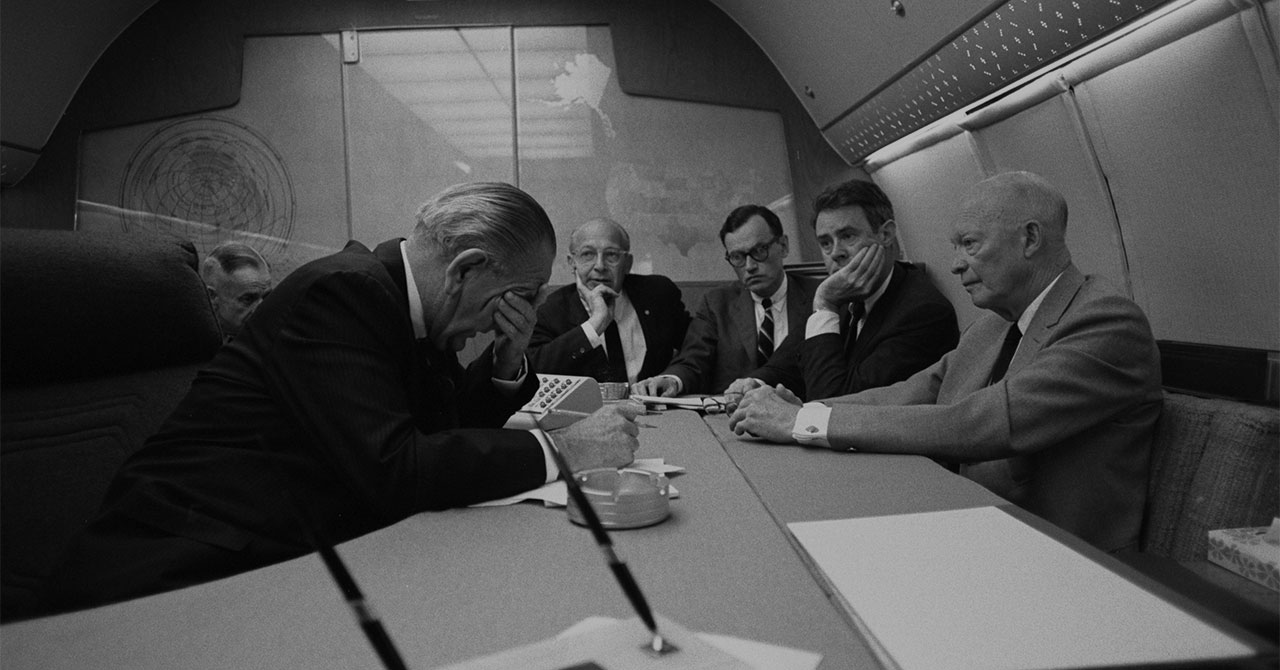 LBJ sitting around a table on Air Force One with former President Eisenhower
